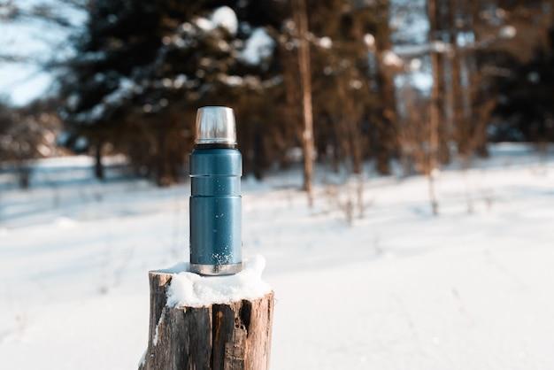 Thermoskanne, die auf einem schneebedeckten baumstumpf in einem winterwald an einem sonnigen tag steht. trekking-konzept, camping Premium Fotos