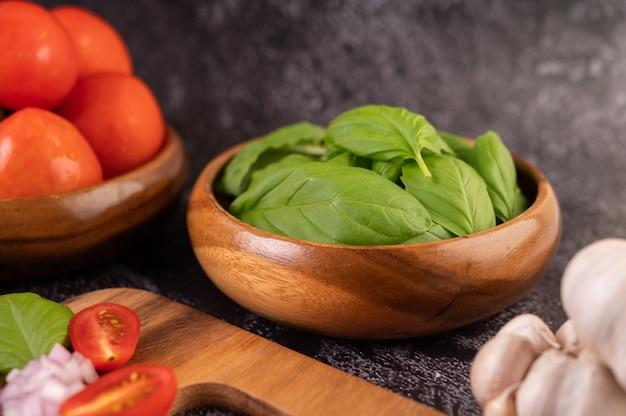 Thymian und tomaten in einer holzschale mit knoblauch auf einem holzschneidebrett. Kostenlose Fotos