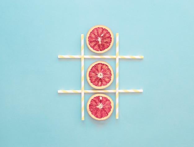 Tic-tac-toe-spiel orange slice, gesunde sommer-konzept, hellblau, minimalismus Premium Fotos