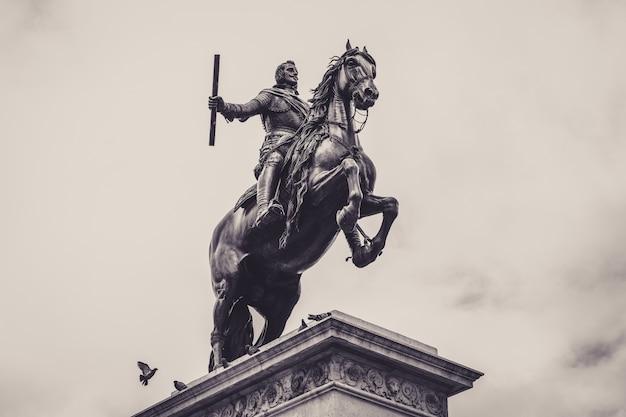 Tiefwinkel-graustufenaufnahme einer statue vor dem königspalast von madrid Kostenlose Fotos