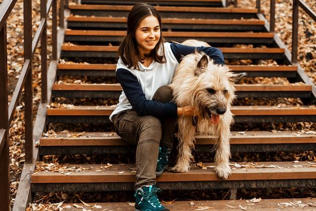 Tiertraining. ein freiwilliges mädchen geht mit einem hund aus einem tierheim. mädchen mit einem hund im herbstpark. gehen sie mit dem hund. sich um die tiere kümmern. Premium Fotos