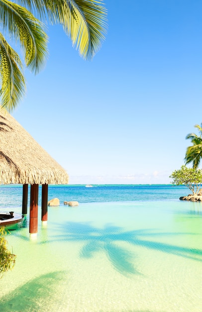 Tiki-hütte und bar am pool des luxushotels an einem hellen sonnigen tag Premium Fotos