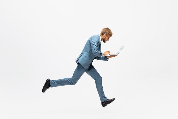 Tippen. mann in bürokleidung läuft, joggt auf leerraum wie profisportler, sportler. ungewöhnlicher blick für geschäftsmann in bewegung, aktion mit ball. sport, gesunder lebensstil, kreativität. Kostenlose Fotos
