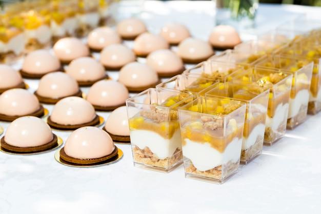 Tisch mit süßigkeiten, dekoriert mit blumen und makronenkuchen und leichten desserts in tassen Premium Fotos
