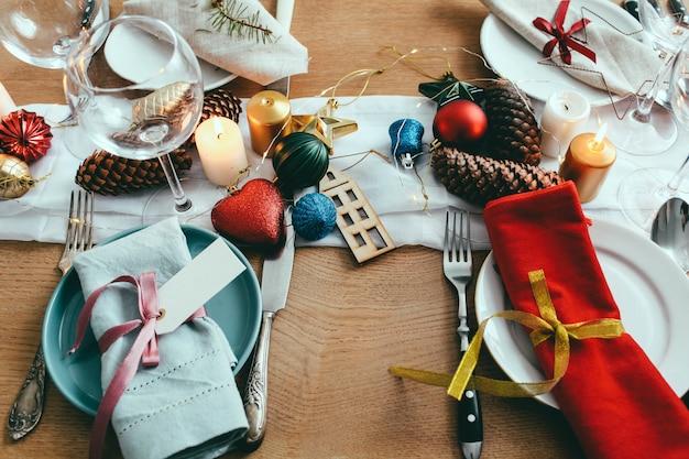 Tisch serviert zum weihnachtsessen im wohnzimmer. schließen sie herauf ansicht, gedeck, platten, niederlassungsdekoration, kerzen und gliterring spielwaren auf holztischhintergrund Premium Fotos