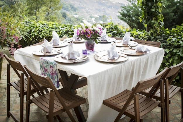 Tisch voller teller und einer blumenvase auf einem schönen balkon mit herrlichem blick Kostenlose Fotos