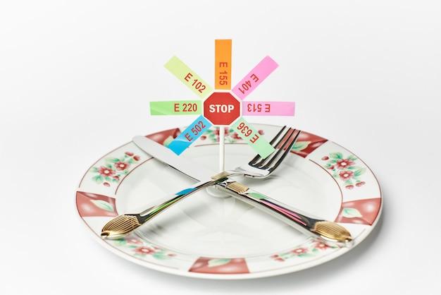 Tischbesteck und stoppschild mit verbotenen zusatzstoffen auf weißem hintergrund Premium Fotos