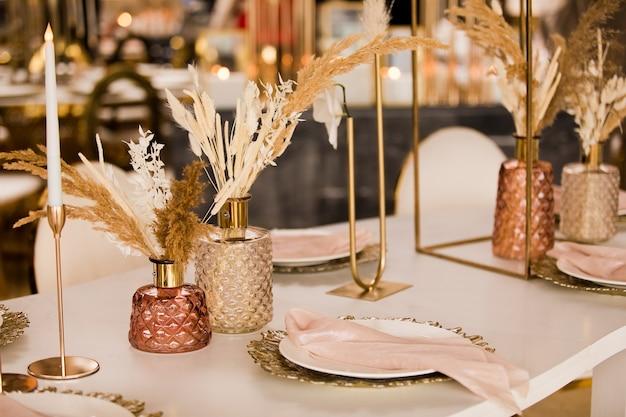 Tischdekoration bei einer luxushochzeit und schöne blumen auf dem tisch. hochzeitsdekor, blumen, rosa und goldenes dekor, kerzen. festliche tischdekoration. Premium Fotos
