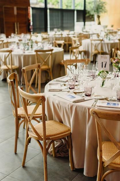 Tische und holzstühle arrangiert und dekoriert in einem hochzeitssaal eines hotels Premium Fotos