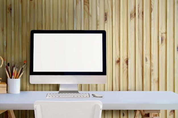 Tischrechner des leeren bildschirms auf weißem schreibtisch über wand im studiobüro. Premium Fotos