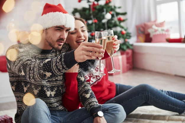 Toast machen. zwei leute sitzen auf dem boden und feiern neujahr Premium Fotos