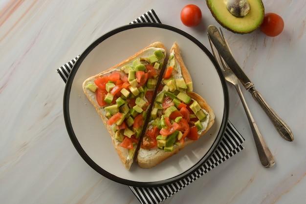 Toast mit frischkäse, avocado und kirschtomaten. gesundes essen. kopieren sie platz. Premium Fotos