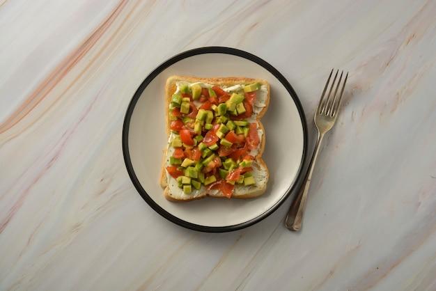 Toast mit frischkäse, avocado und kirschtomaten. gesundes essen. Premium Fotos