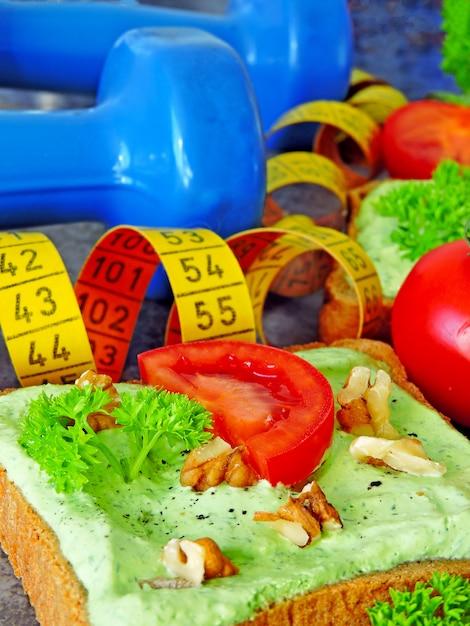 Toast mit grünem hüttenkäse und walnüssen und tomate. maßband. hanteln. fitness essen. Premium Fotos