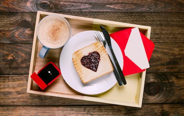 Toast mit marmelade auf teller in der nähe von besteck, tasse getränk, umschlag und ring in geschenkbox an bord Kostenlose Fotos