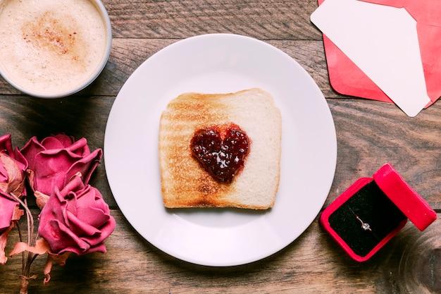 Toast mit marmelade auf teller in der nähe von getränk, blumen, umschlag und ring in geschenkbox Kostenlose Fotos