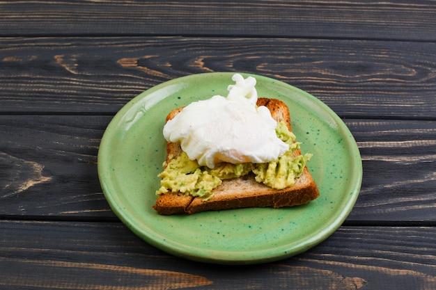 Toast und poschiertes ei mit avocado auf einer grünen platte auf holztisch Premium Fotos