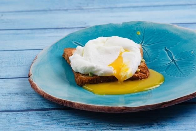 Toast und poschiertes ei mit avocado auf einer platte auf holztisch Premium Fotos