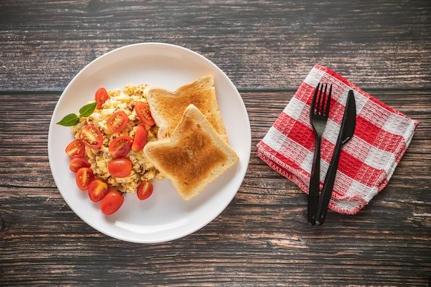 Toastbrot mit durcheinandergemischten eiern und kirschtomate auf einem holztisch und einer roten serviette Premium Fotos