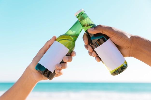 Toasten mit zwei flaschen in der nähe von meer Kostenlose Fotos