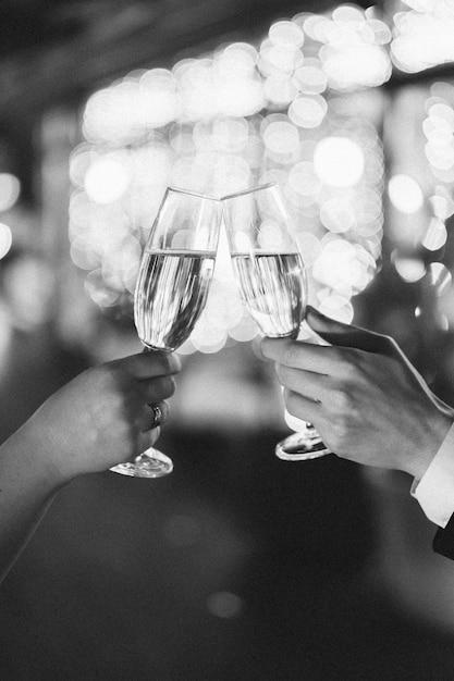 Toasten von gläsern auf einem verschwommenen hintergrund. seitenansicht schwarz und weiß Kostenlose Fotos