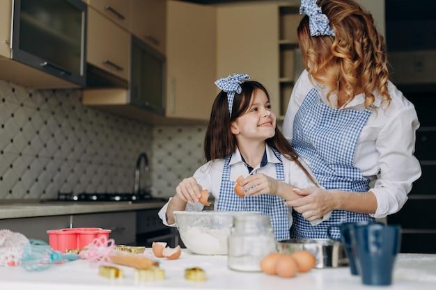 Tochter brechen ein ei und schaut die mutter mit einem lächeln an. Premium Fotos