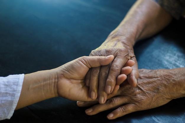 Tochter, die hand der älteren mutter hält, die alzheimer- und parkinson-patient ist Premium Fotos