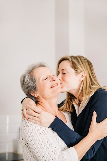 Tochter, die Mutter am Muttertag küsst Kostenlose Fotos