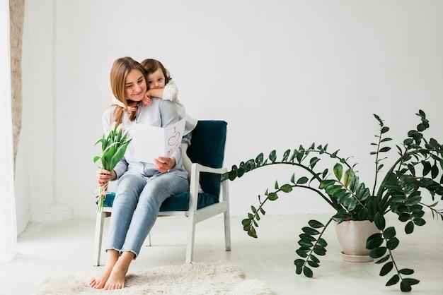 Tochter, die mutter mit grußkarte umarmt Kostenlose Fotos