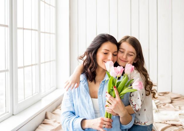 Tochter, die mutter mit tulpen umarmt Kostenlose Fotos