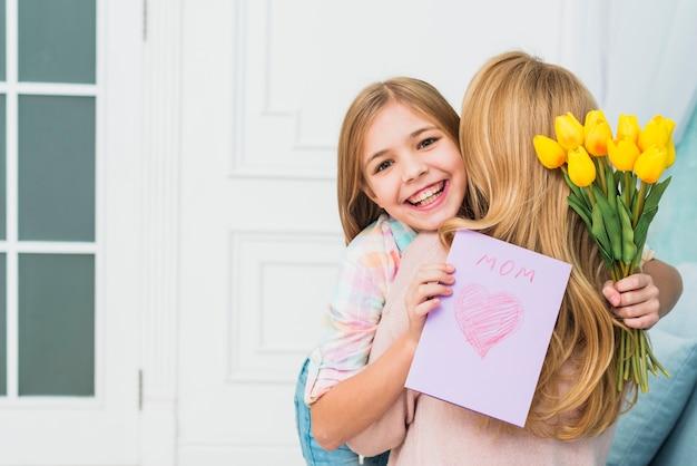Tochter mit geschenken lächelnd und mutter umarmt Kostenlose Fotos
