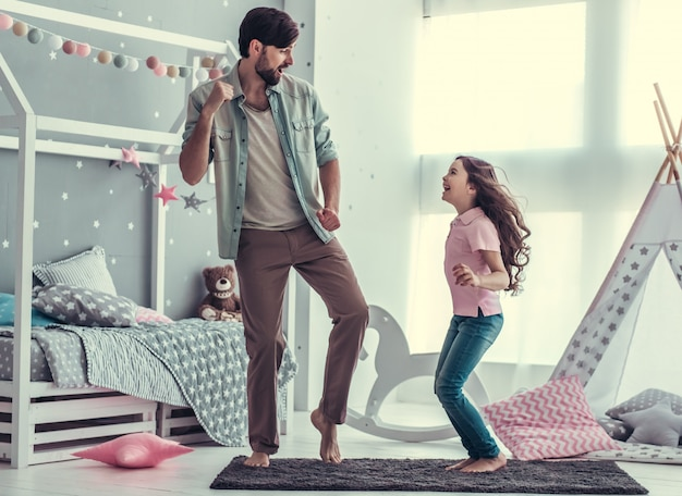 Tochter und ihr hübscher vater tanzen und lächeln. Premium Fotos