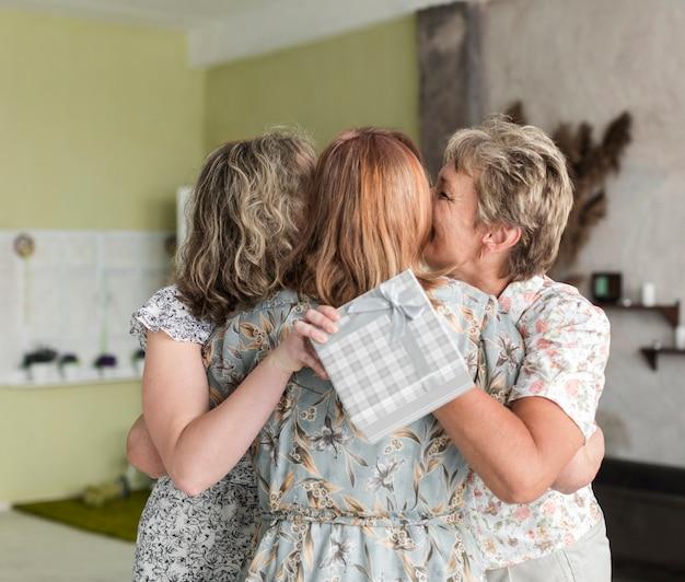 Tochter und mutter, die ältere frau mit dem halten der geschenkbox küssen Kostenlose Fotos