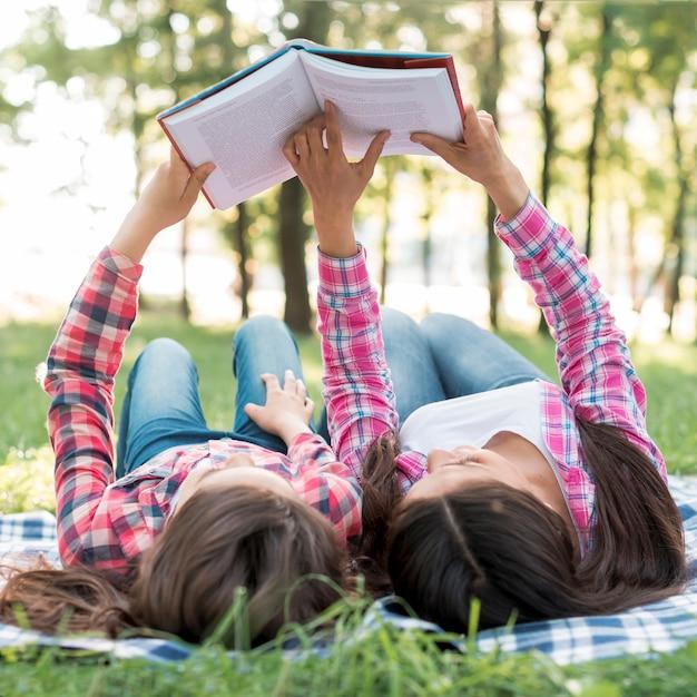 Tochter und mutter, die auf decke während des lesebuches im park liegen Kostenlose Fotos