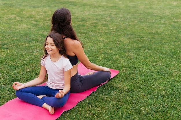 Tochter und mutter, die auf grünem gras meditieren Kostenlose Fotos