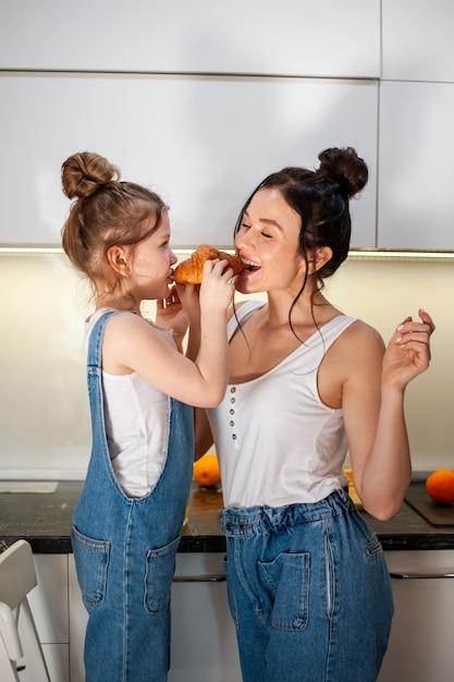 Tochter und mutter teilen sich ein leckeres croissant Kostenlose Fotos