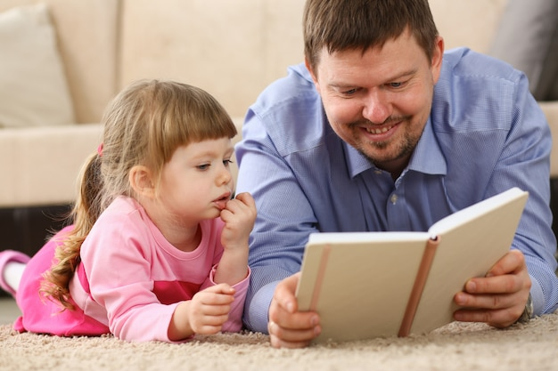 Tochtervater-lesebuch, das auf teppich liegt Premium Fotos