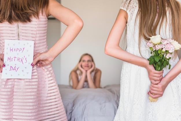Töchter, die grußkarte und blumen für mutter halten Kostenlose Fotos