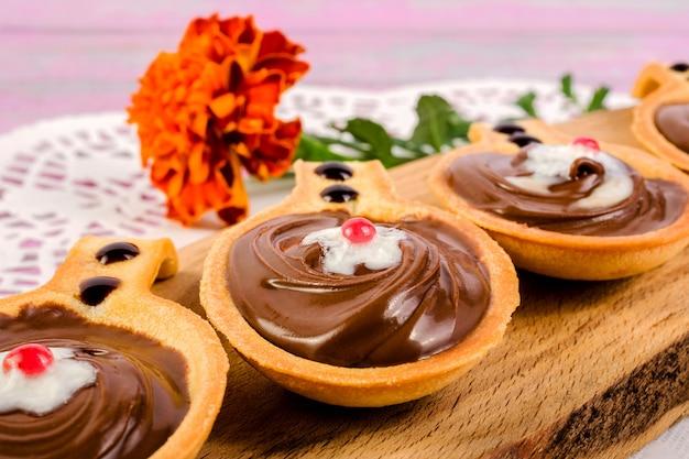 Törtchen in form von löffeln, mit süßer schokoladenhaselnusspaste auf einem schneidebrett. Premium Fotos