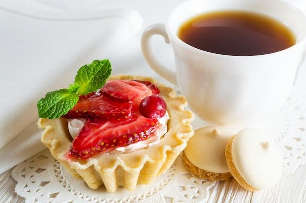 Törtchen mit frischen erdbeeren und frischkäse, einer tasse tee und kleinen keksen. Premium Fotos