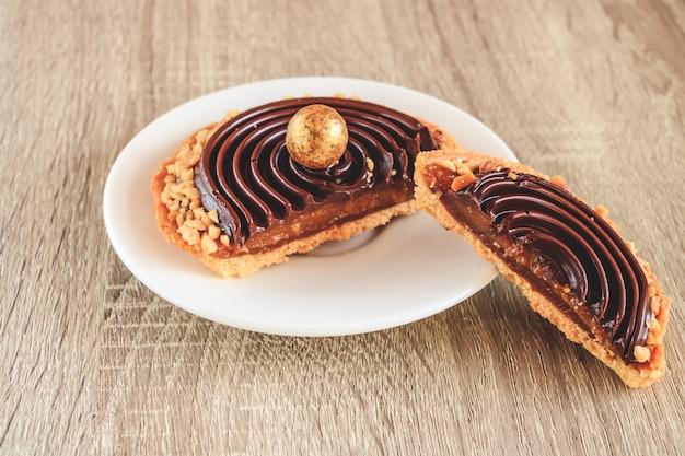 Törtchen mit karamell überzogen mit schokolade und mit nusschips dekoriert. Premium Fotos