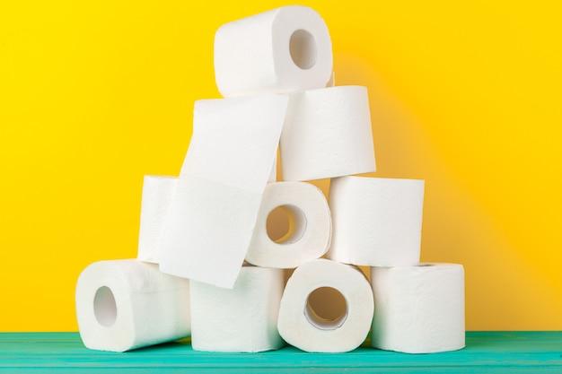Toilettenpapierrollen gestapelt gegen gelben hintergrund Premium Fotos