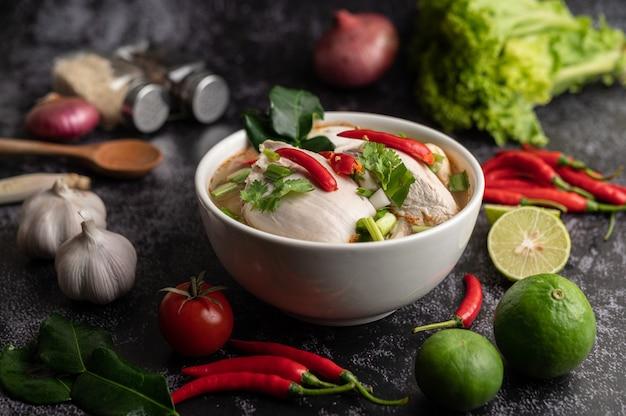 Tom yum huhn mit chili, koriander, getrocknetem chili, kaffirlimettenblättern, pilzen und zitronengras in einer schüssel Kostenlose Fotos