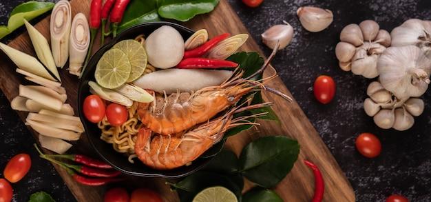 Tom yum kung in einer schüssel mit tomaten-, chili-, zitronengras-, knoblauch-, zitronen- und kaffirlimettenblättern Kostenlose Fotos