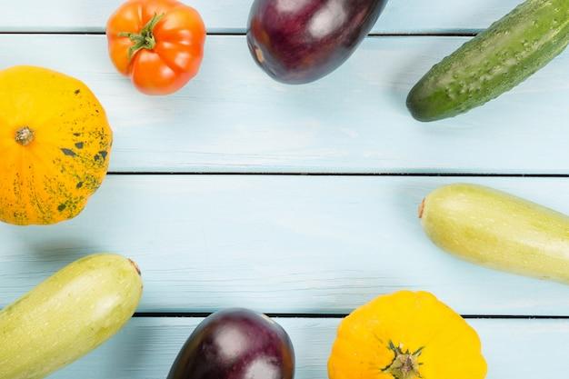 Tomate, gurken, buschkürbise, auberginen und mark auf blauem holztisch mit copyspace hintergrund Premium Fotos