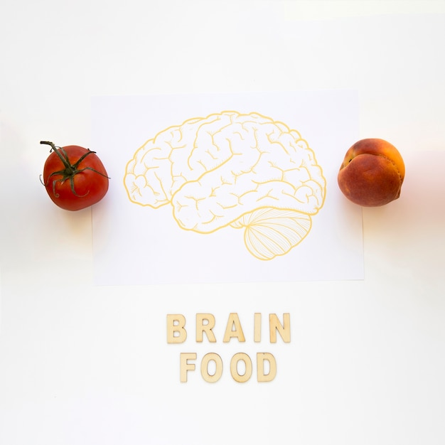 Tomate und pfirsich nahe gehirnlebensmittelwörtern mit dem zeichnen auf papier Kostenlose Fotos