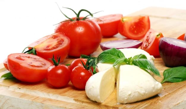 Tomaten, basilikum und mozzarella auf holzbrett Kostenlose Fotos