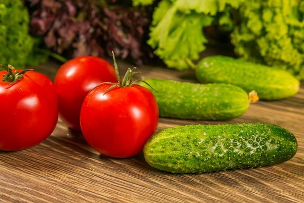 Tomaten und gurken auf einem holztisch Premium Fotos
