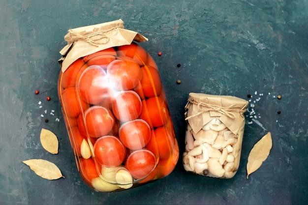 Tomaten und pilze in einem glas auf schwarzem hintergrund, draufsicht. hausgemachte konfitüren. Premium Fotos