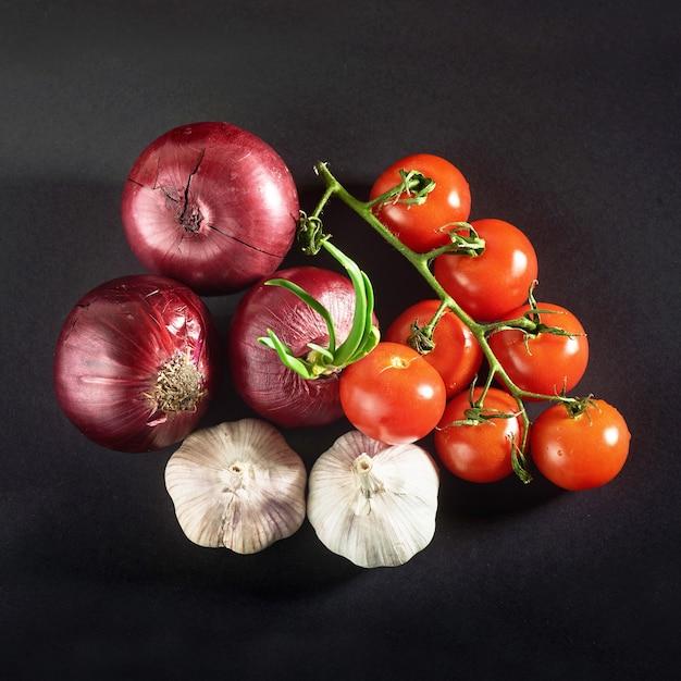 Tomaten, zwiebeln und knoblauch sind schwarz isoliert Kostenlose Fotos